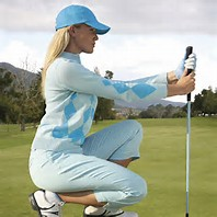 golf apparel sale - Picture of a female lining her putt up on the green